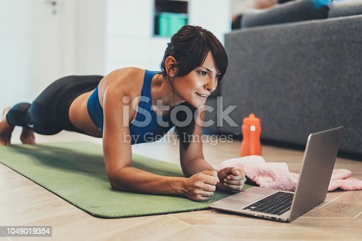925799546 istock photo Sporty woman doing plank in front of her laptop 1049019354