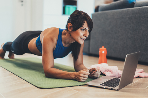 istock Sporty woman doing plank in front of her laptop 1049019354