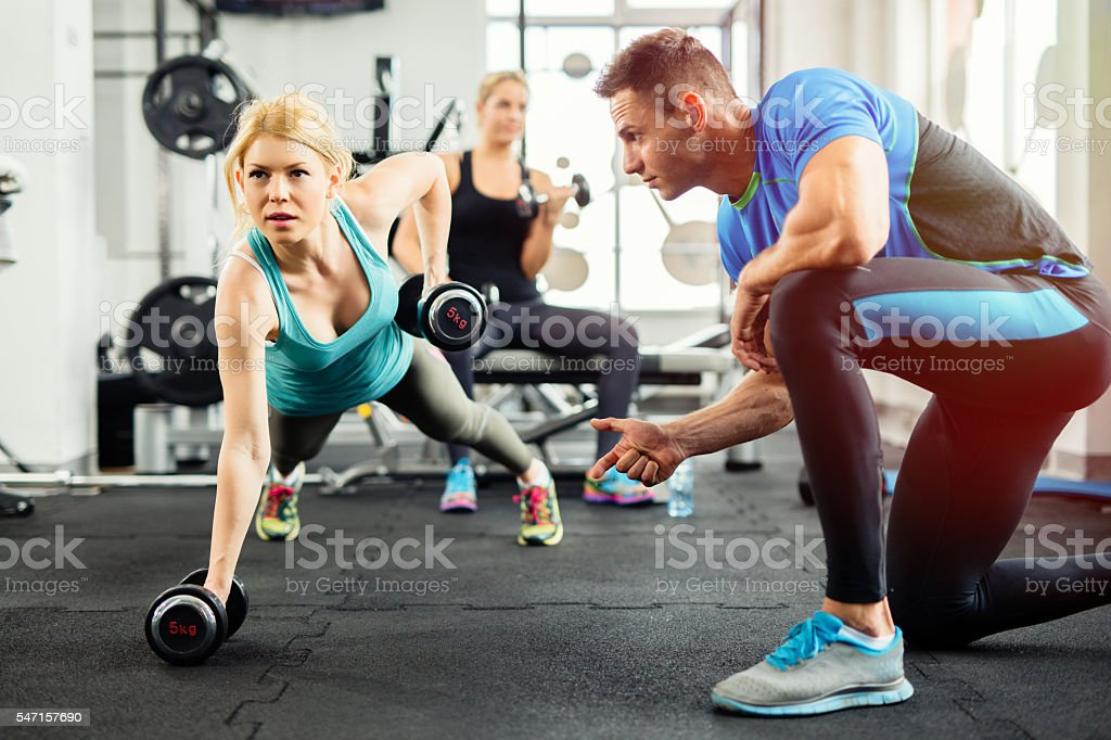 Sporty woman doing push-ups under supervision of  personal trainer. - foto stock
