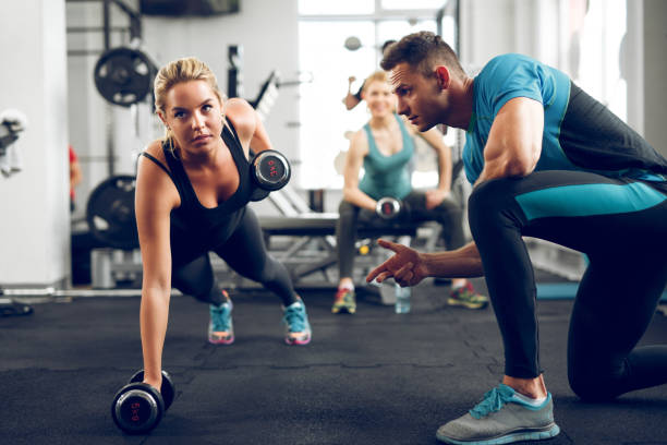 deportiva mujer haciendo flexiones bajo la supervisión del entrenador personal. - entrenador personal fotografías e imágenes de stock