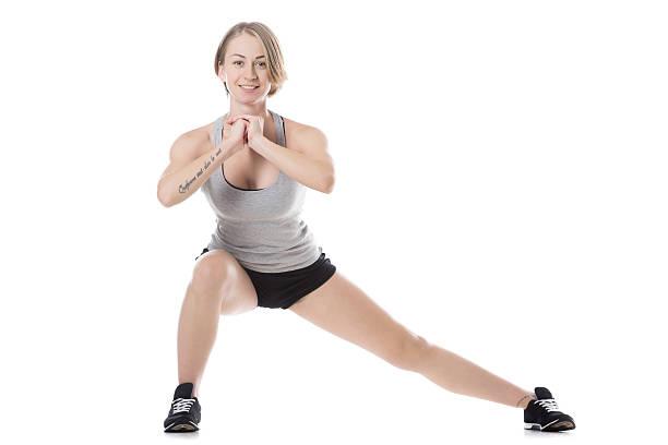 sportliche frau beim seitlichen ausfallschritt - gymnastik tattoo stock-fotos und bilder
