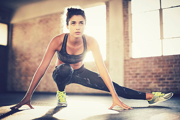 Sporty woman doing stretching exercise before workout in gym stock photo