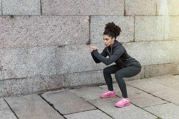 Sporty woman doing warm up squat, stretching near a wall - foto de acervo