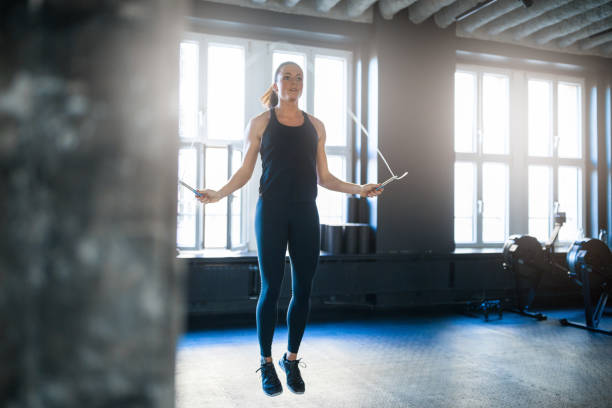 Sporty woman doing workout with jump rope in gym stock photo