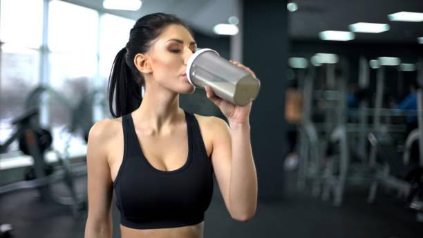 sportliche frau trinken protein-shake nach dem training, muskelaufbau ernährung, gesundheit - nahrungsergänzungsmittel stock-fotos und bilder