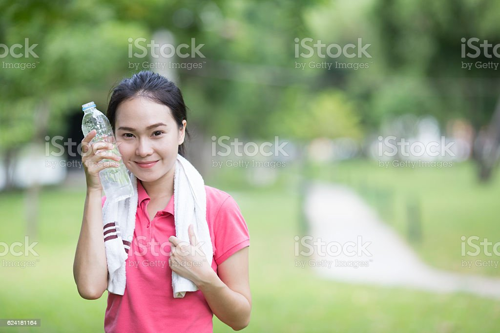 sporty woman drinking water from a bottle stock photo