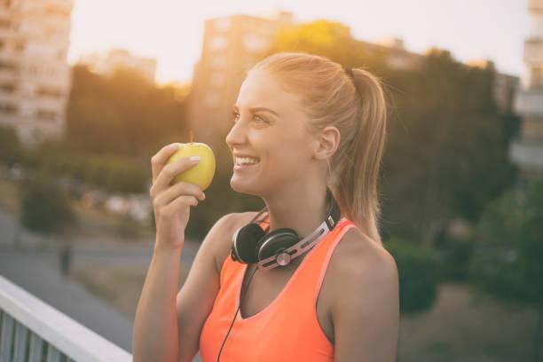 sportliche frau essen apfel - spielabend snacks stock-fotos und bilder