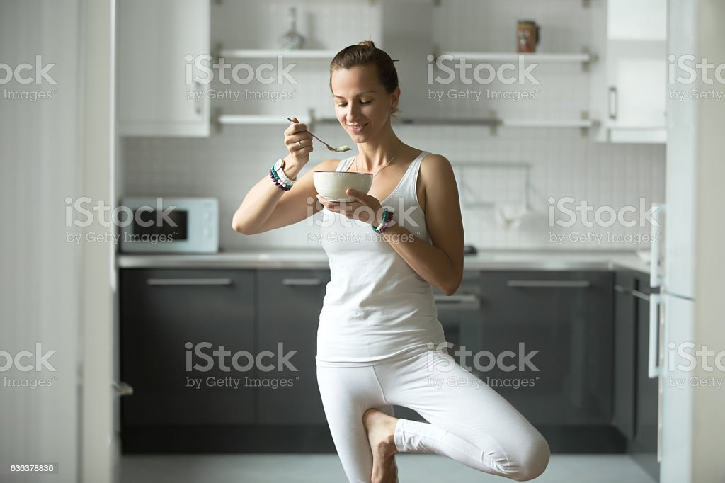 Sporty woman eating in Tree pose stock photo