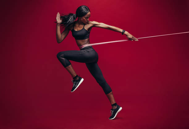 Sporty woman exercising with resistance band stock photo