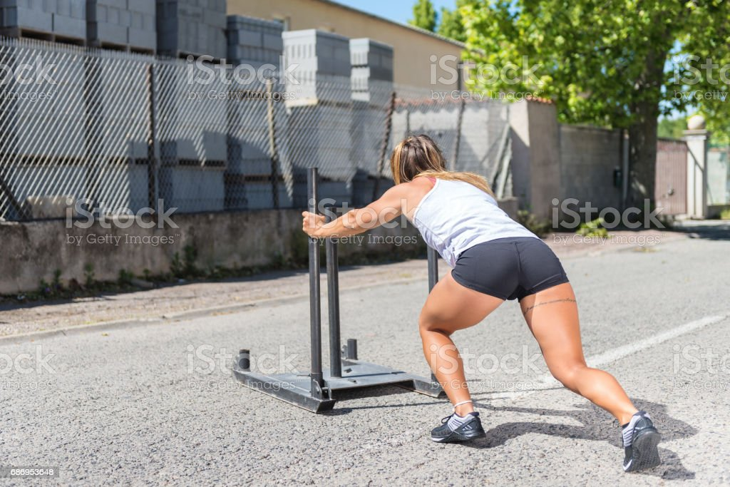 Sporty woman exercising with sled outside stock photo