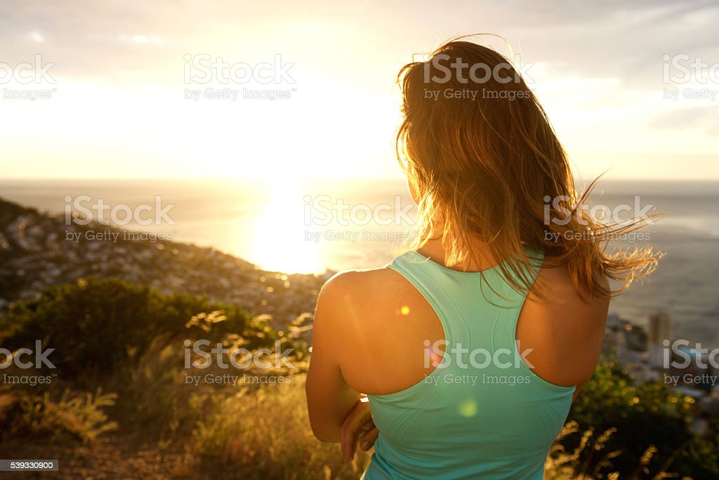 Sporty woman from behind watching the sunset stock photo
