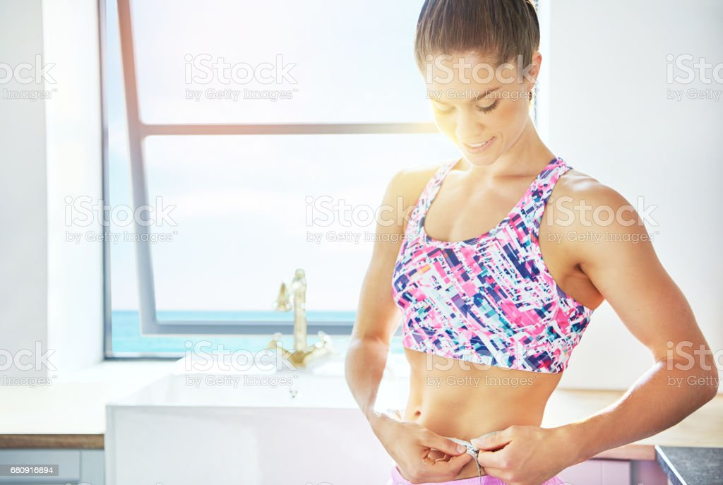 Sporty woman in sunlight measuring her beltline royalty-free stock photo