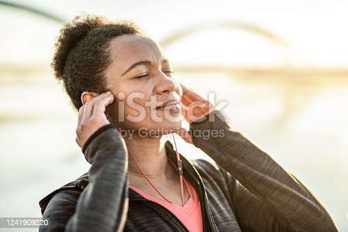 Happy Athletic African American Woman Listening to Music Outdoors on Waterside and Day Dreaming.