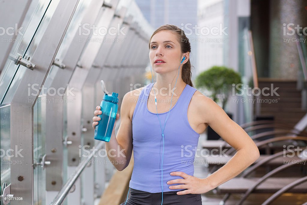 Sporty Woman Listening to Music on Terrace of Gym stock photo