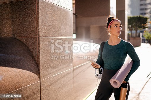 1091470492 istock photo Sporty woman listening to music over the wireless earphones in an urban area 1082375860