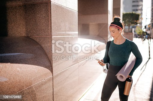 istock Sporty woman listening to music over the wireless earphones in an urban area 1091470492