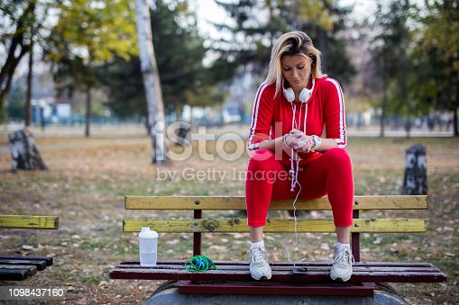Sporty woman listening to the music in pubic park