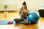 Sporty woman in sport's clothing eating salad and sitting on sport's mat near weights and sport's ball at home