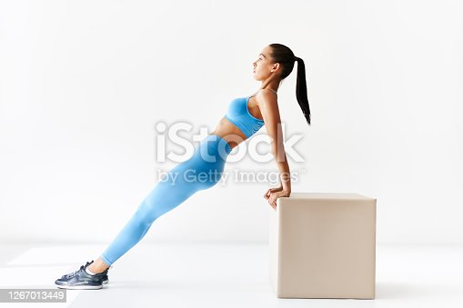 Sporty woman making reverse plank exercise on white background. sport, fitness and people concept