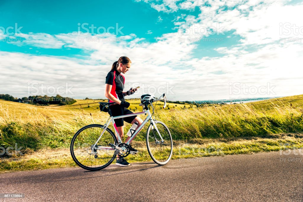 Sporty woman on racing bicycle uses mobile phone while exercising on country road