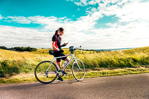 istock Sporty woman on racing bicycle uses mobile phone while exercising on country road 861175694