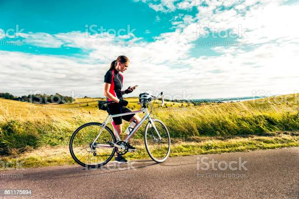 Photo of Sporty woman on racing bicycle uses mobile phone while exercising on country road