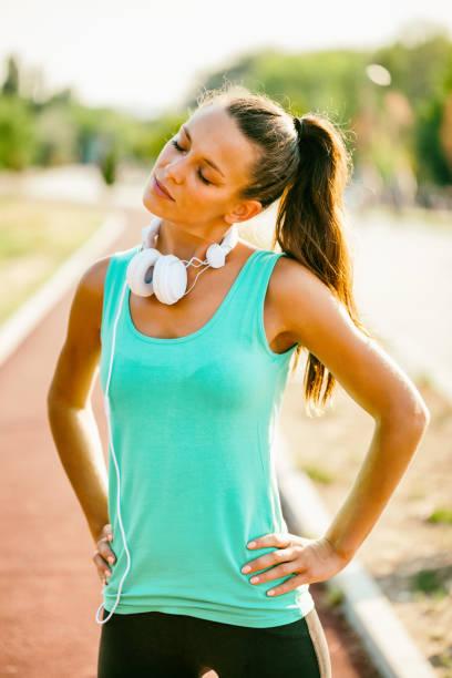sportliche frau outdoor - hals übungen stock-fotos und bilder