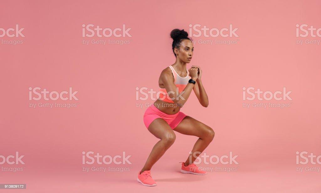 Desportiva mulher praticando o exercício de agachamento - foto de acervo