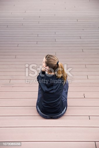 istock Sporty woman resting on the stairs outdoors 1073085056