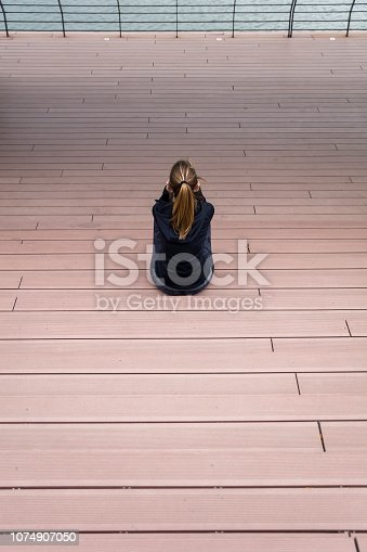 istock Sporty woman resting on the stairs outdoors 1074907050