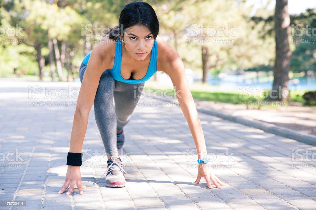 Sporty woman runner in start position stock photo