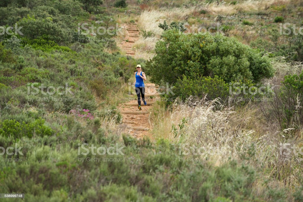 Sporty woman running downhill stock photo