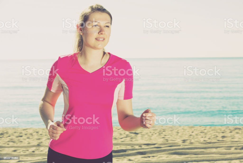 Sporty woman running on ocean beach royalty-free stock photo