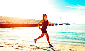 Sporty female runs on a beach in a tropical climate while the sun shines. Her exercising is pushing her endurance for marathon running or a triathlon. She looks calm, as she runs in the heat.