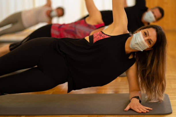 sporty woman smiling behind the mask during fitness training stock photo