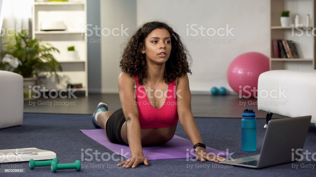 Sporty woman stretching after home workout, online fitness training,...