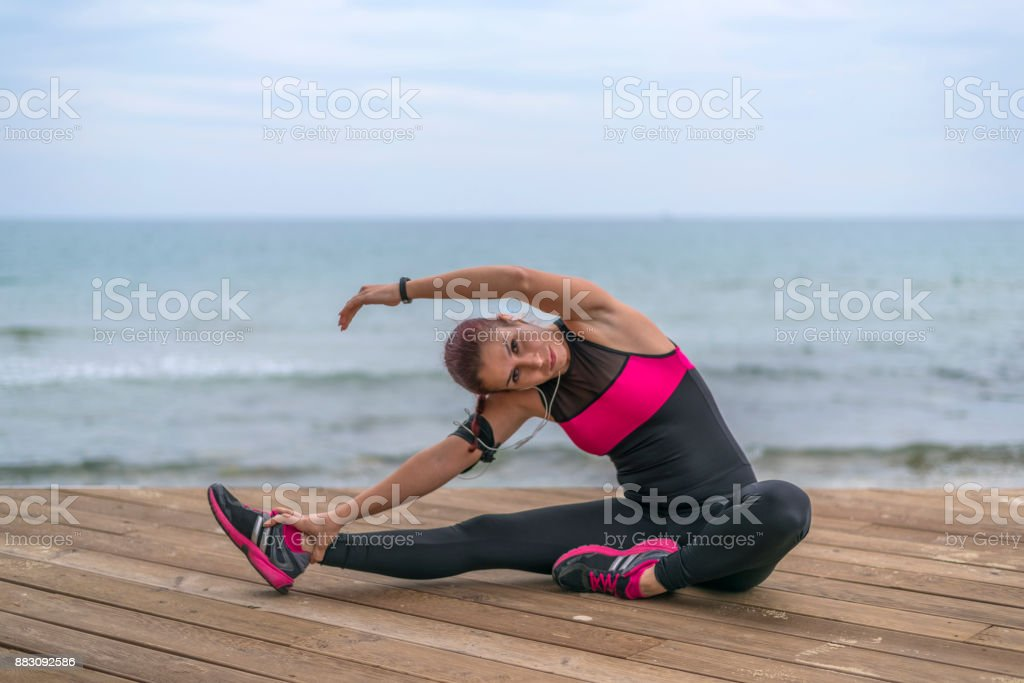 Sporty woman stretching legs on the pier floor stock photo