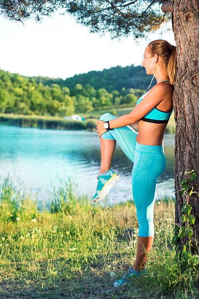 sportlich frau dehnen beine - schlanke waden stock-fotos und bilder