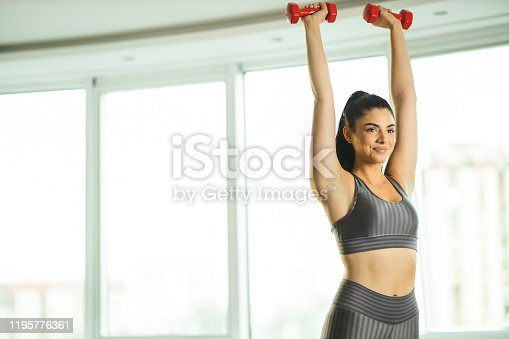 1035512048istockphoto Sporty woman stretching with dumbbells 1195776361