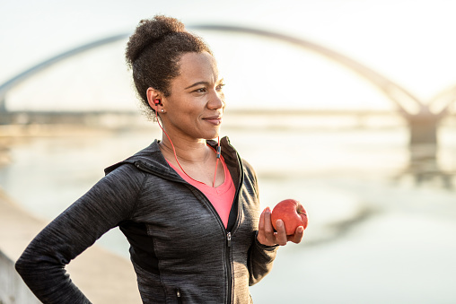 Happy African American Athletic Woman Eating An Apple After Exercise.