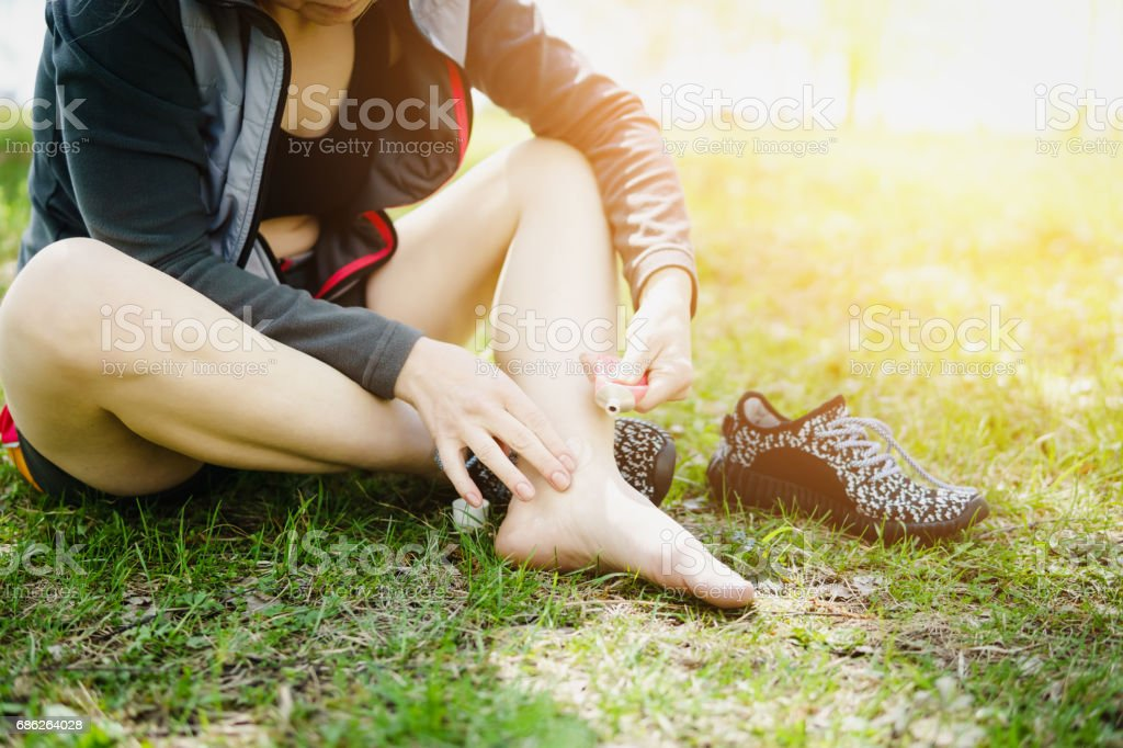 Sporty woman treating her foot ankle. Injury. stock photo
