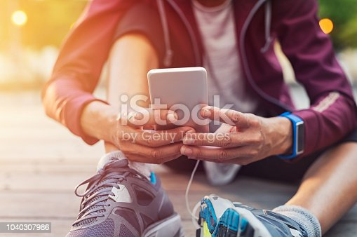 istock Sporty woman using mobile phone 1040307986