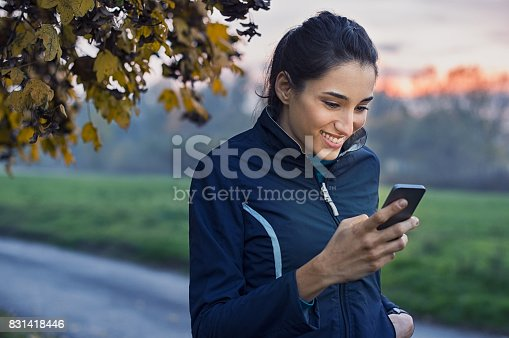 istock Sporty woman using phone 831418446