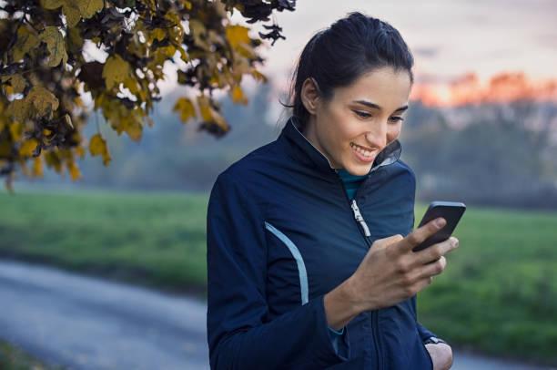 sportliche frau mit telefon - outdoor handy stock-fotos und bilder