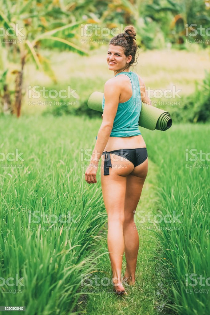 Sporty Woman Walking on Meadow and Turning Round stock photo