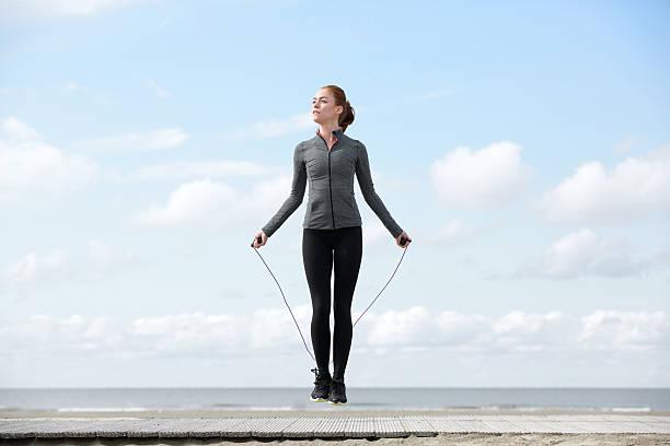 sportliche frau aufwärmen mit springseil - leinenhosen frauen stock-fotos und bilder
