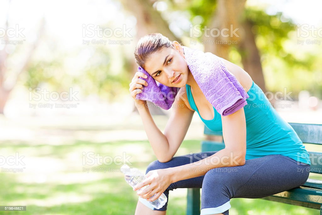 Sporty Woman Wiping Sweat On Park Bench stock photo