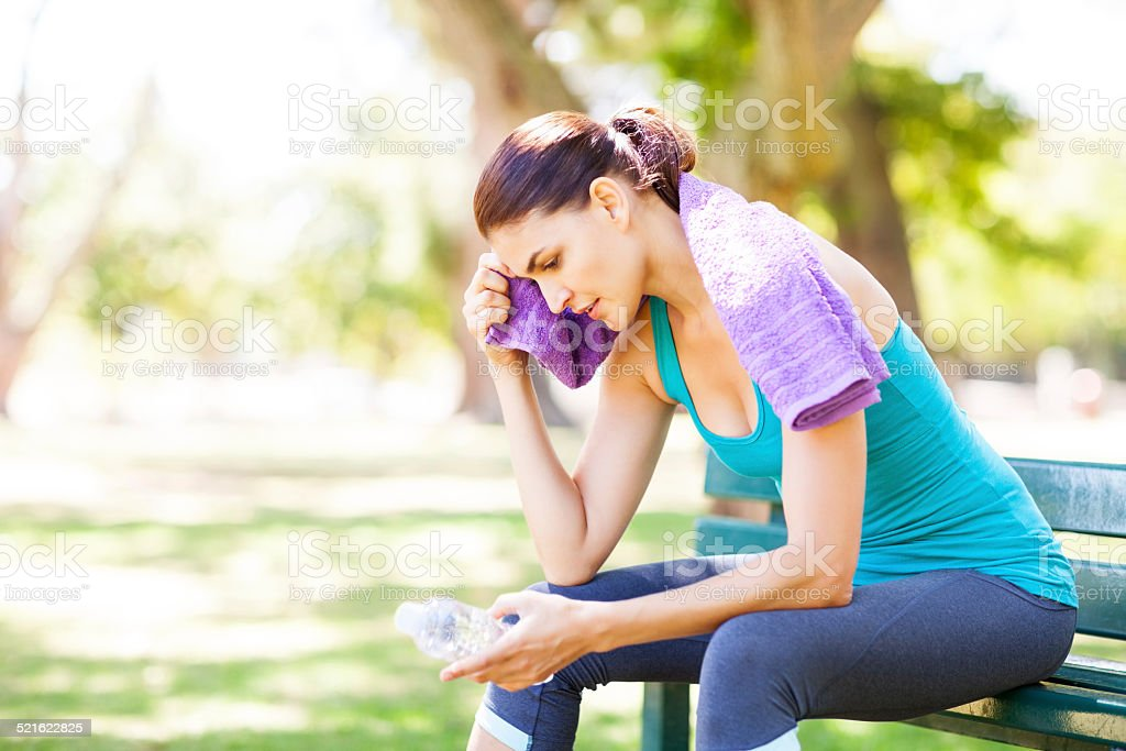 Sporty Woman Wiping Sweat With Towel On Park Bench stock photo