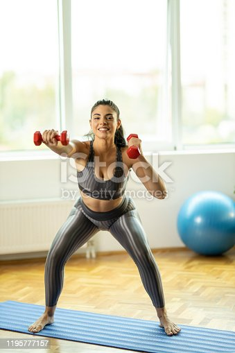 1035512048istockphoto Sporty woman with dumbbells 1195777157