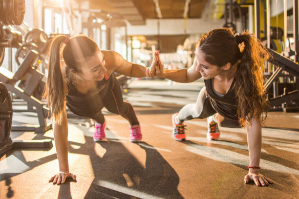 Sporty women giving high five to each other while working out together at gym. stock photo